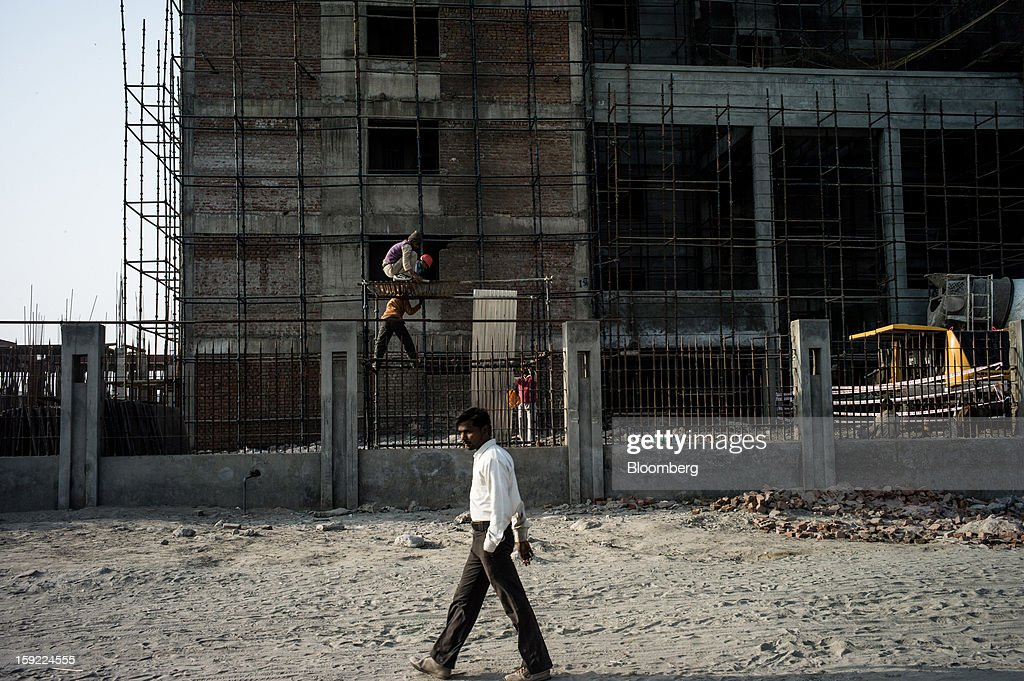 A man walks past an apartment block under construction in Noida, Uttar Pradesh, India, on Wednesday, Jan. 9, 2013. India's Finance Ministry predicts GDP growth of as little as 5.7 percent in the year to March 31, the least in a decade. Photographer: Sanjit Das/Bloomberg via Getty Images