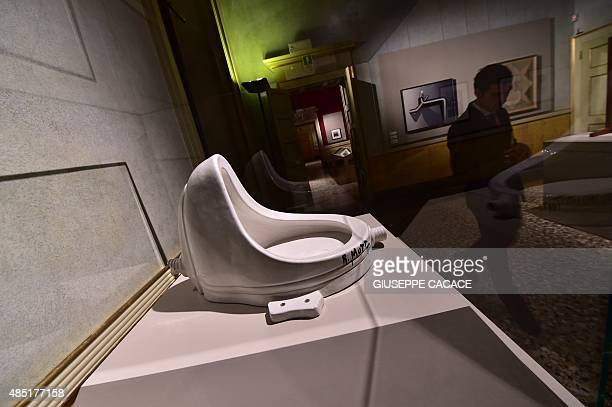 A man walks past an art piece named 'Fontaine' created in 1917 by French artist Marcel Duchamp as part of the exhibition 'La Grande Madre' on August...