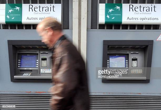 A man walks past an ATM machine of the French Bank BNP Paribas on October 16 2008 in Paris French stocks plunged 495 percent in initial trading hit...