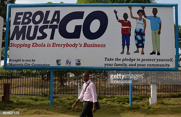 A man walks past an ebola campaign banner with the new slogan 'Ebola Must GO' in Monrovia on February 23 2015 The country of four million is slowly...