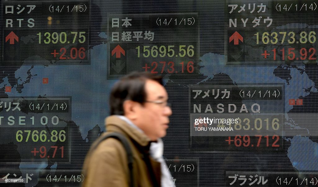 A man walks past an electric quotation board flashing the Nikkei key index of the Tokyo Stock Exchange (TSE) in front of a securities company in Tokyo on January 15, 2014. Tokyo stocks rose 1.77 percent early on January 15, tracking a rise on Wall Street that was driven by a better-than-expected report on US December retail sales. AFP PHOTO/Toru YAMANAKA