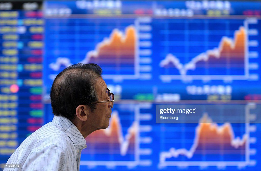 A man walks past an electronic monitor displaying graphs of various market indices outside a securities firm in Tokyo, Japan, on Friday, Aug. 23, 2013. Japanese shares rose, with the Topix index halting three days of losses, as exporters advanced after the yen weakened against the dollar. Photographer: Yuriko Nakao/Bloomberg via Getty Images