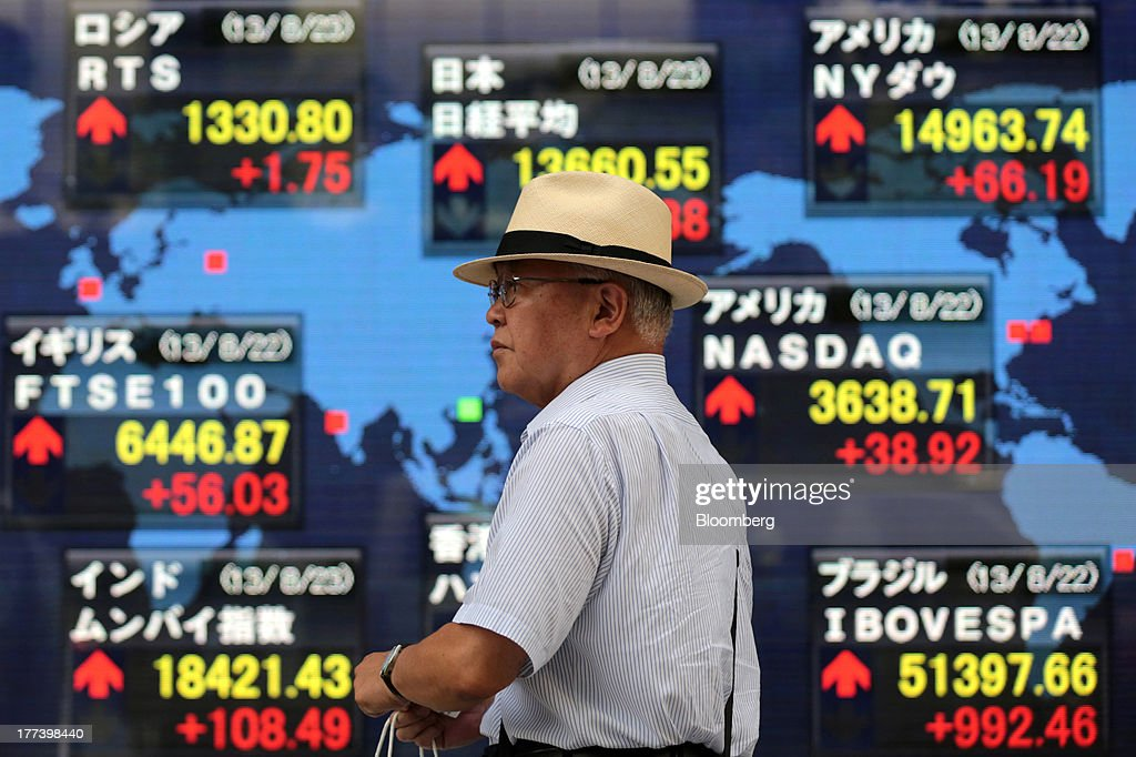 A man walks past an electronic monitor displaying the closing figure of the Nikkei 225 Stock Average, center top, outside a securities firm in Tokyo, Japan, on Friday, Aug. 23, 2013. Japanese shares rose, with the Topix index halting three days of losses, as exporters advanced after the yen weakened against the dollar. Photographer: Yuriko Nakao/Bloomberg via Getty Images