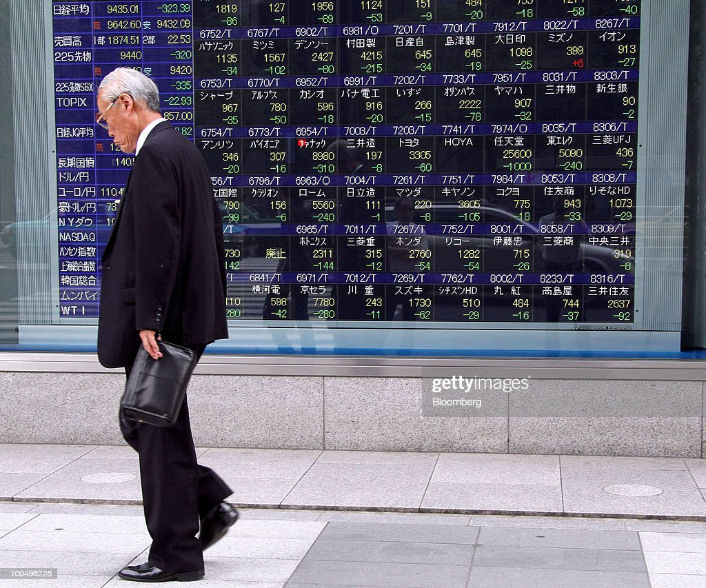 A man walks past an electronic stock board outside a securities firm in Tokyo, Japan, on Tuesday, May 25, 2010. Japanese stocks fell, dragging the Nikkei 225 Stock Average to its lowest close in almost six months on growing signs European financial institutions are facing stress and as the yen rose against the euro and dollar. Photographer: Haruyoshi Yamaguchi/Bloomberg via Getty Images