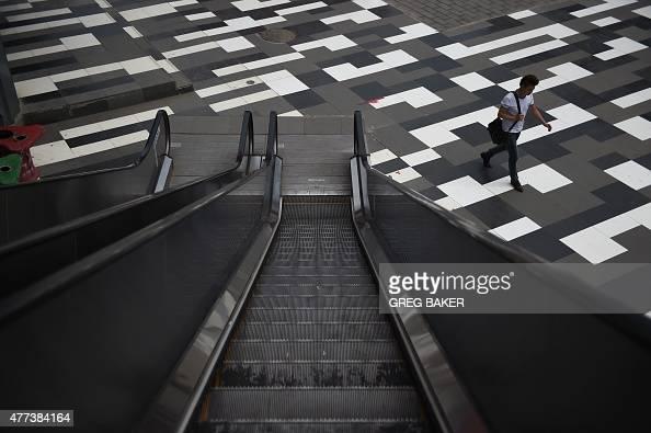 A man walks past an escalator at a shopping mall in Beijing on June 17 2015 AFP PHOTO / GREG BAKER