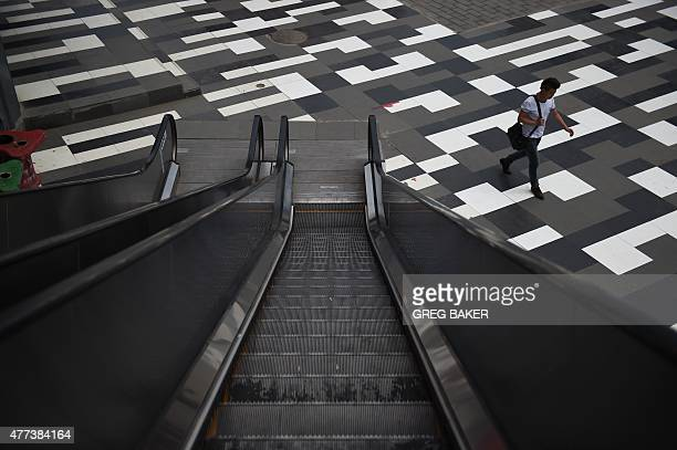 A man walks past an escalator at a shopping mall in Beijing on June 17 2015 AFP PHOTO / GREG BAKER