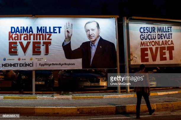 A man walks past an Evet' campaign poster showing the portrait of Turkish President Recep Tayyip Erdogan on April 14 2017 in Sanliurfa Turkey...