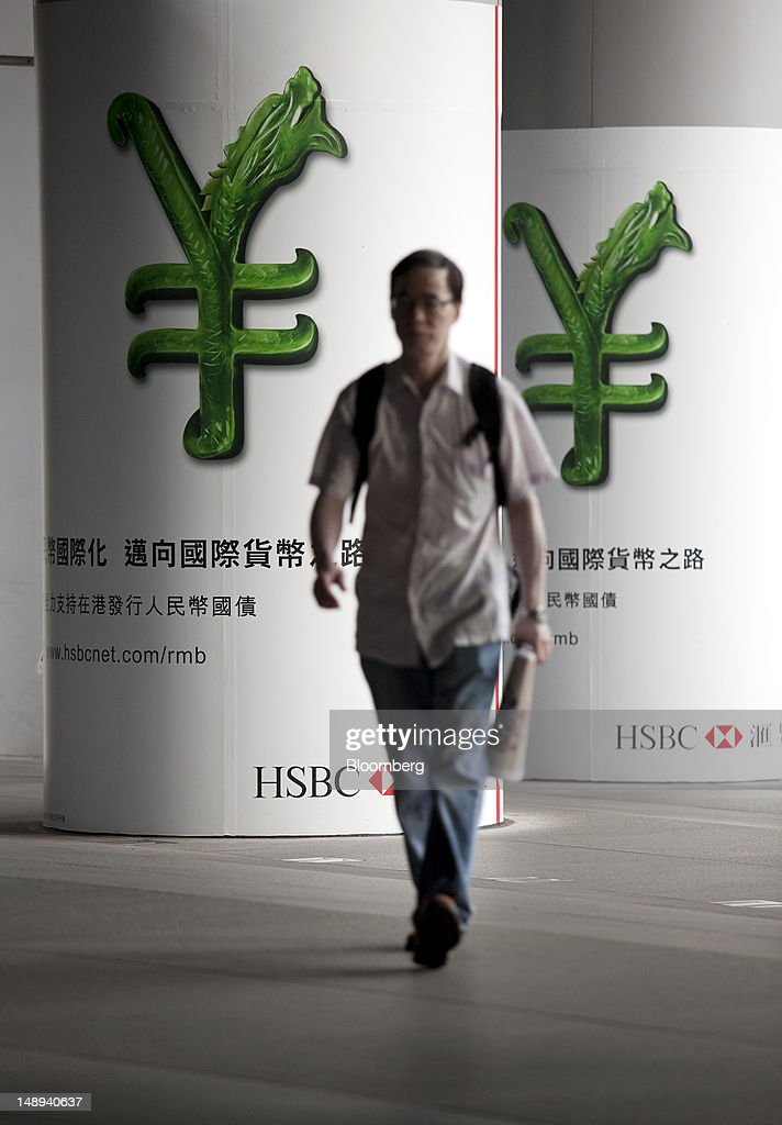 A man walks past an HSBC advertisement showing a Renminbi currency symbol outside the HSBC Holdings Plc headquarters in Hong Kong, China, on Friday, July 20, 2012. Asian currencies had a second weekly advance on speculation the U.S. and China will adjust policies to revive the world's two biggest economies, boosting demand for riskier assets. Photographer: Jerome Favre/Bloomberg via Getty Images