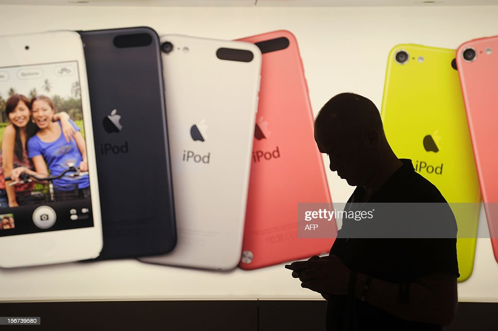 A man walks past an illuminated display outside an Apple store in Hong Kong on November 20, 2012. Global sales of 'smart devices,' which include smartphones and tablets, will hit 821 million worldwide this year and 1.2 billion in 2013, a research firm said. AFP PHOTO / ANTHONY WALLACE
