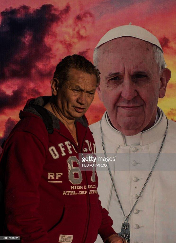 A man walks past an image of Pope Francis, in Mexico City on February 12, 2016 hours before the arrival of the pontiff to the country. Pope Francis left Rome on Friday bound for Cuba, where he is to hold a historic meeting Russian Patriarch Kirill before continuing on to Mexico for a five-day visit. AFP PHOTO / Pedro PARDO / AFP / Pedro PARDO
