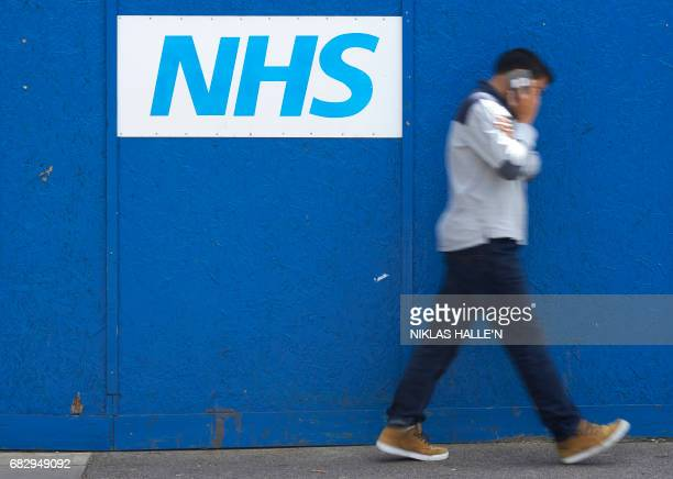 A man walks past an NHS signage outside The Royal London Hospital in London on May 14 2017 The unprecedented global cyberattack has hit more than...
