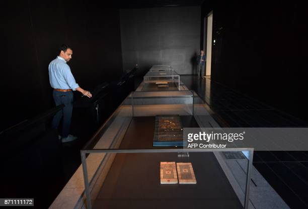 A man walks past an old Koran on display in a gallery at the Louvre Abu Dhabi Museum during a media tour on November 6 2017 prior to the official...