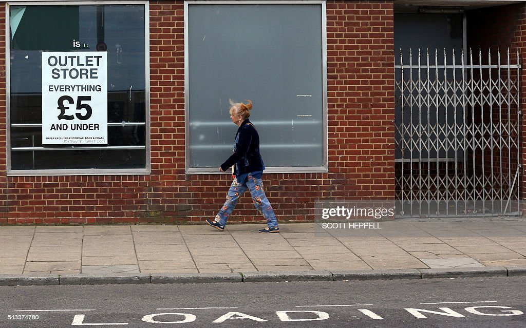 A man walks past an outlet store in Redcar, north east England on June 27, 2016 Thursday's dramatic vote to quit the European Union was driven by millions of people in the post-industrial north and centre of England, in working-class towns like Redcar, on the northeast coast. The strength of feeling may have stunned metropolitan Britain, but came as no surprise in places like Redcar, where 66.2 percent ultimately voted to leave the EU. / AFP / Scott Heppell / TO