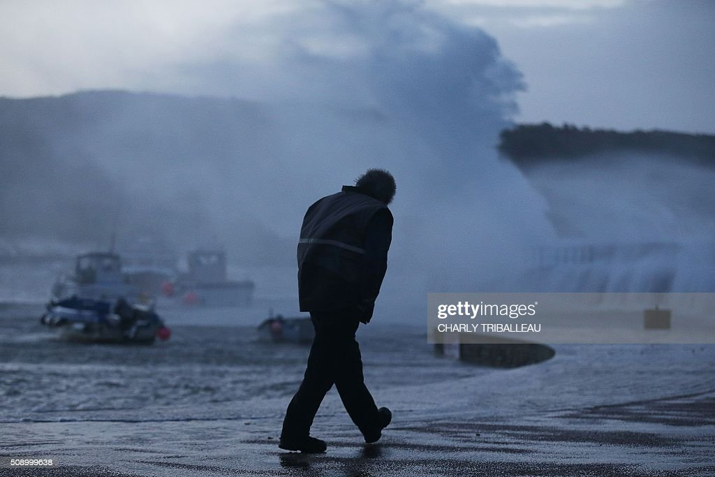 A man walks past anchored boat in a harbour in Auderville, northwestern France, on February 8, 2016, as strong winds hit the region. Winds of over 130 kh/h were recorded in the region where 16 departments have been placed under alert for for wind and flooding waves. / AFP / CHARLY TRIBALLEAU