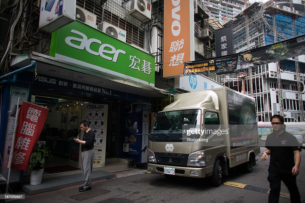 A man walks past another man standing under Acer Inc. signage displayed outside an electronics store on Bade Road in Taipei, Taiwan, on Wednesday, Nov. 6, 2013. Acer, Taiwans second-largest computer maker, plunged to a 12-year low in Taipei trading after announcing a record loss, job cuts and the resignation of J.T. Wang as chief executive officer. Photographer: Lam Yik Fei/Bloomberg via Getty Images