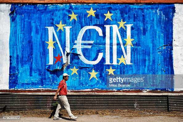 A man walks past antiEU graffiti on June 30 2015 in Athens Greece Greek voters will decide in a referendum next Sunday on whether their government...