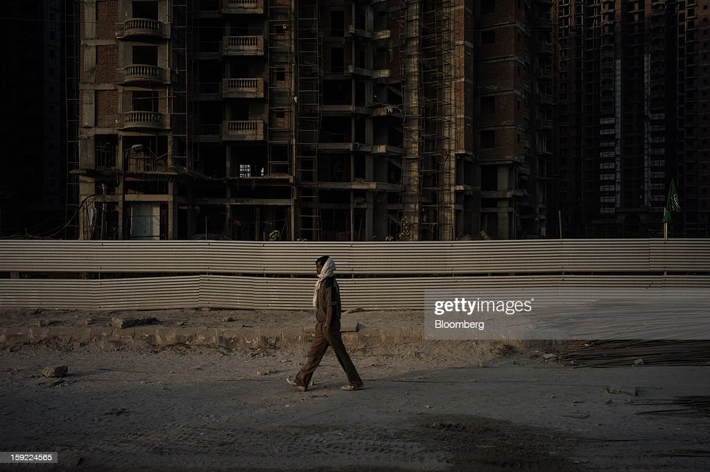 A man walks past apartment blocks under construction in Noida, Uttar Pradesh, India, on Wednesday, Jan. 9, 2013. India's Finance Ministry predicts GDP growth of as little as 5.7 percent in the year to March 31, the least in a decade. Photographer: Sanjit Das/Bloomberg via Getty Images