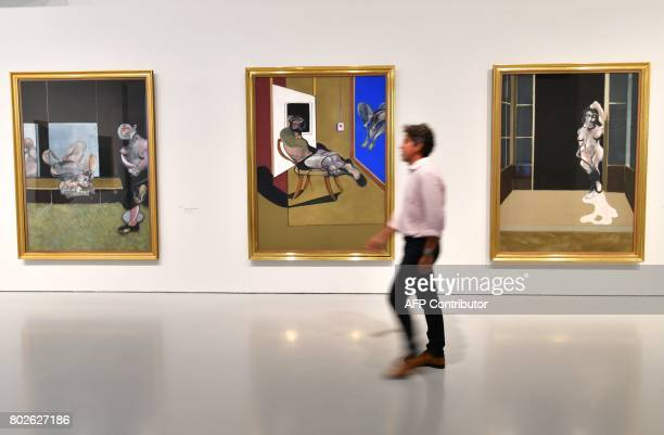 A man walks past artworks 'Female nude standing in a doorway' 'Seated figure' and 'Study from the human body' by late British painter Francis Bacon...