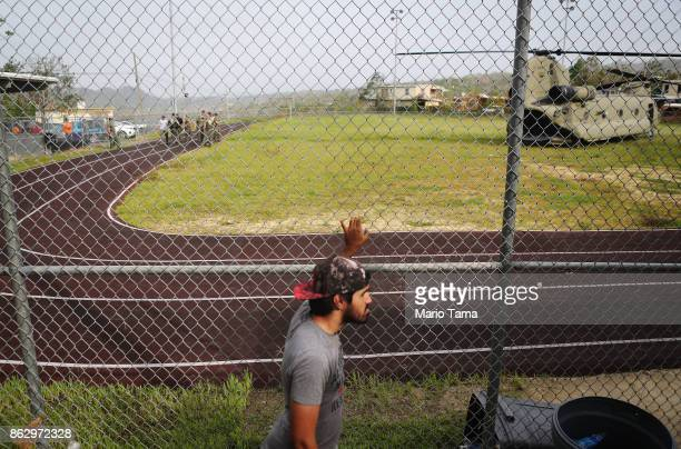 A man walks past as US Army soldiers prepare to offload food and water from a helicopter during recovery efforts four weeks after Hurricane Maria...