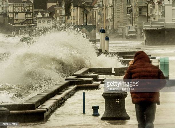 A man walks past as waves break against the Wimereux breakwaterin Wimereux northern France on February 9 2016 High winds buffeted northwestern Europe...