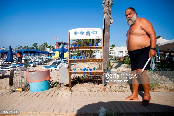 A man walks past ashtrays made available for tourists at a beach in the resort town of Ayia Napa in southeastern Cyprus on September 7 2017 With more...