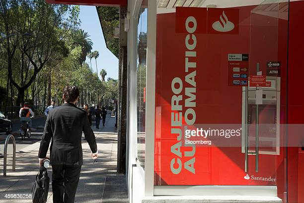 A man walks past automated teller machines outside a Banco Santander SA bank branch in Mexico City Mexico on Thursday Nov 27 2014 Santander Mexico...