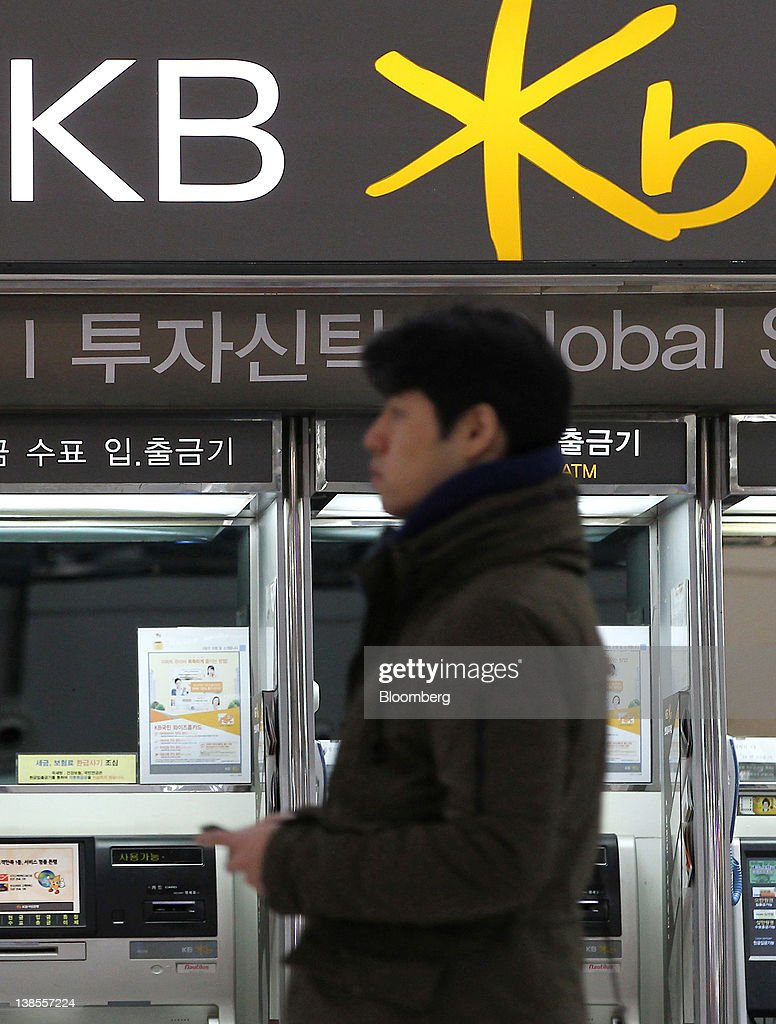 A man walks past automatic teller machines (ATM) at a Kookmin Bank branch in Seoul, South Korea, on Thursday, Feb. 9, 2012. KB Financial Group Inc., owner of South Korea's largest lender, posted its lowest quarterly profit in a year on increased provisions for bad debts. Photographer: SeongJoon Cho/Bloomberg via Getty Images