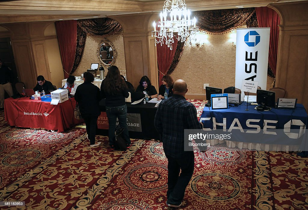A man walks past Bank of America Corp., Wells Fargo & Co., and JPMorgan Chase & Co. booths during registration at the Neighborhood Assistance Corporation of America (NACA) event in Los Angeles, California, U.S., on Friday, March 28, 2014. Fed buying of the securities that helped spur a housing recovery is poised to fall below growth in the $5.5 trillion government-backed market as soon as May, Nomura Holdings Inc. said. Last year, the Fed added twice as much of the debt as was created, suppressing yields that guide mortgage interest rates. Photographer: Patrick T. Fallon/Bloomberg via Getty Images