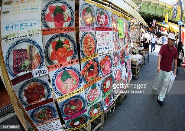 A man walks past beside a menu of Japanese restaurant at at Ameyoko market in Tokyo Japan Sep 2013 Ameyoko is a bustling outdoor marketplace and...