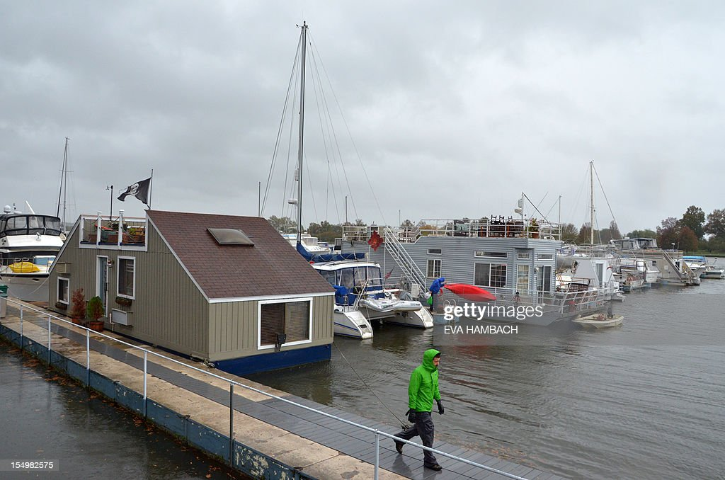 A man walks past boat houses in the Capitol Yacht Club Marina on the Potomac river in downtown Washington, DC October 29, 2012 ahead of Hurricane Sandy's expected landfall farther up north on the Eastern Seaboard later in the day. Much of the eastern United States was in lockdown mode awaiting the arrival of a hurricane dubbed 'Frankenstorm' that threatened to wreak havoc on the area with storm surges, driving rain and devastating winds. AFP PHOTO Eva HAMBACH
