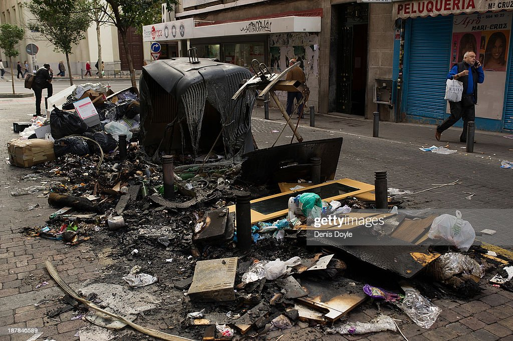 A man walks past burnt bins that were overflowing with rubbish in the city centre on November 13, 2013 in Madrid, Spain. Street cleaners, garbage collectors and public park gardeners working for Madrid city council started an indefinite strike 9 days ago over the private contractor's plan to axe more than 1,000 jobs and introduce a 40% pay cut for the remaining workers.
