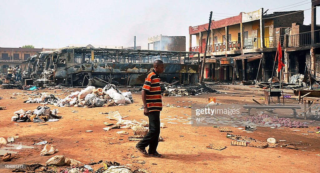 A man walks past burnt buses at New Road bus station in Sabon Gari district in northern Nigeria's largest city of Kano on March 19, 2013. Two suicide bombers rammed their car into a bus laden with passengers at the motor park, killing at least 22 people and injuring 65 others, and the following explosion burnt five buses.