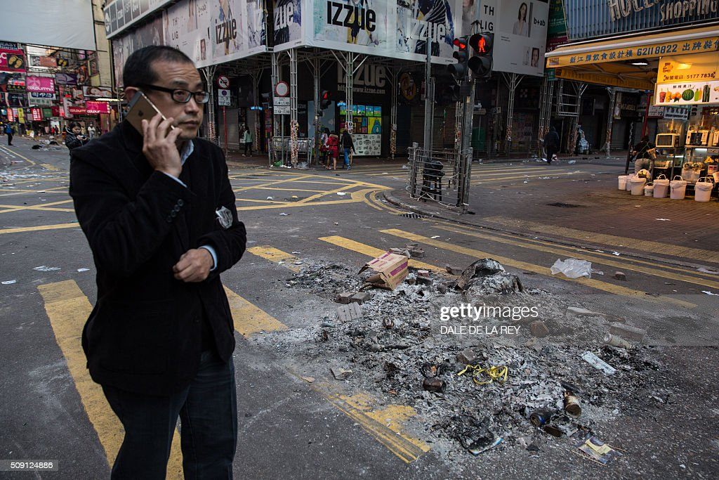 A man walks past burnt debris following overnight clashes between protesters and police in the Mongkok area of Hong Kong on February 9, 2016. Baton-wielding Hong Kong riot police fired warning shots and tear gas early on February 9 after a riot erupted in the busy district of Mongkok when officials tried to shift illegal hawkers, local radio reported. AFP PHOTO / DALE DE LA REY / AFP / DALE de la REY