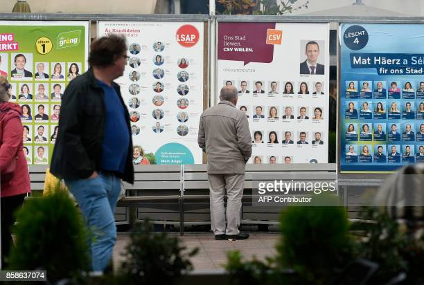 A man walks past campaign posters of the Green Party Socialist Party Social Christian Party and Liberal Party on October 7 on the eve of the...