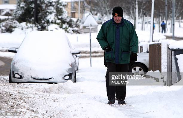A man walks past cars covered in snow in Londonderry Northern Ireland on January 14 2015 More than 100 schools and nurseries have been shut and many...