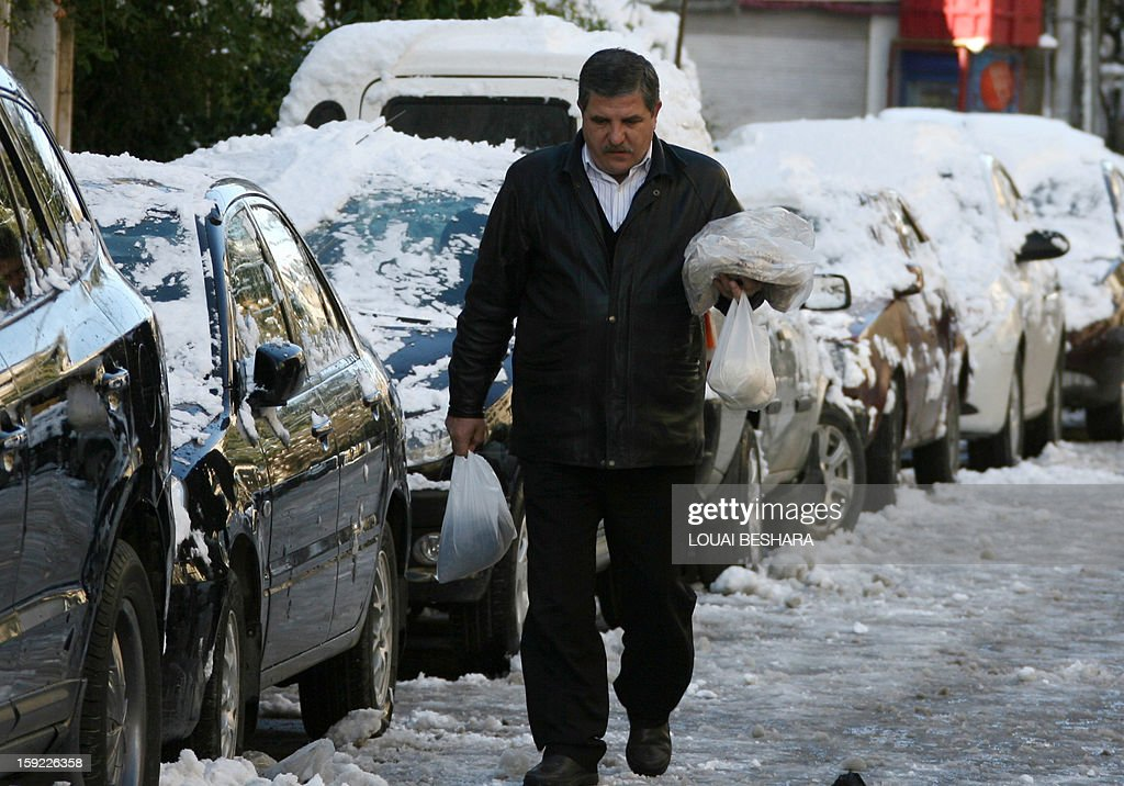 A man walks past cars covered with snow on January 10, 2013 in the Syrian capital of Damascus. Snow carpeted Syria's war-torn cities but sparked no let-up in the fighting, instead heaping fresh misery on a civilian population already enduring a chronic shortage of heating fuel and daily power cuts.