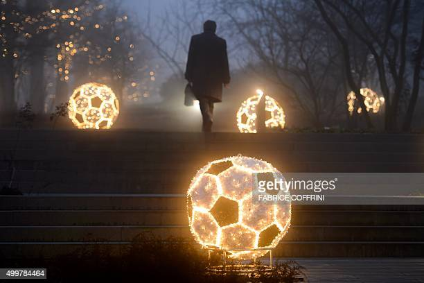 A man walks past Christmas decorations as he leaves the FIFA headquarters on December 3 2015 in Zurich The unprecedented corruption scandal engulfing...