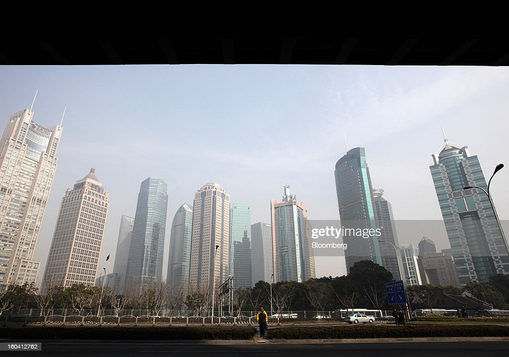 A man walks past commercial buildings in the Pudong area of Shanghai, China, on Wednesday, Jan. 30, 2013. China's economic growth accelerated for the first time in two years as government efforts to revive demand drove a rebound in industrial output, retail sales and the housing market. Photographer: Tomohiro Ohsumi/Bloomberg via Getty Images