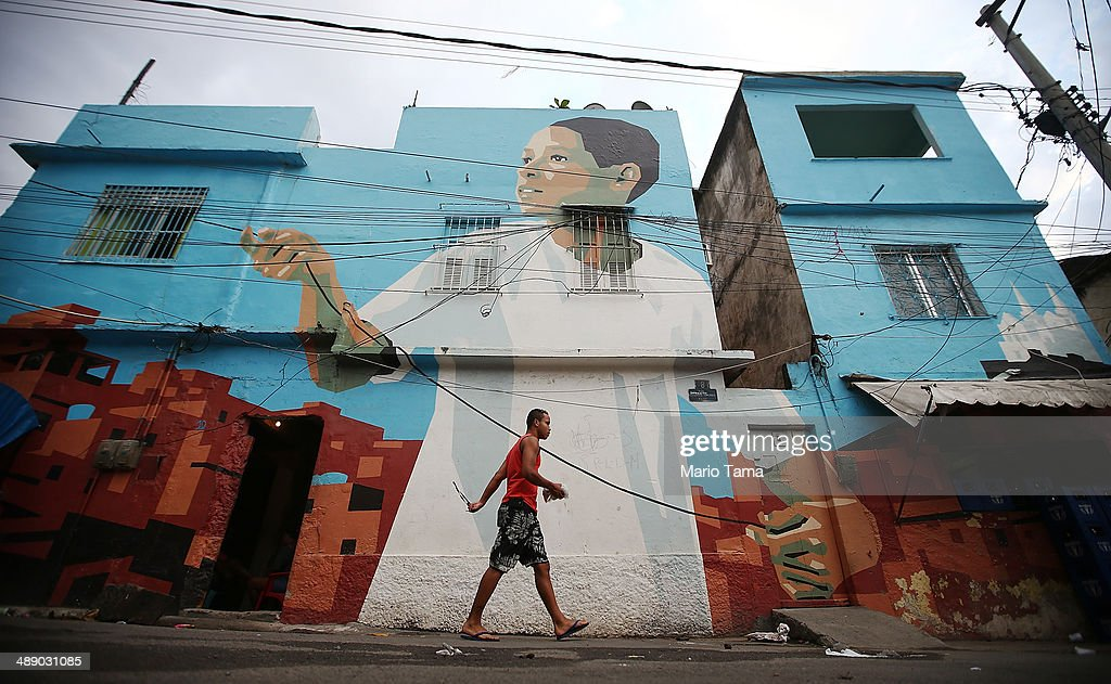 A man walks past community artwork painted by Dutch artists Jeroen Koolhaas and Dre Urhahn (Haas&Hahn) in the Vila Cruzeiro shanty town on May 9, 2014 in Rio de Janeiro, Brazil. Public and private art projects are sprucing up a number of slums, or 'favelas', across the city. The city is attempting to build a number of infrastructure projects ahead of the 2014 FIFA World Cup and Rio 2016 Olympic Games.