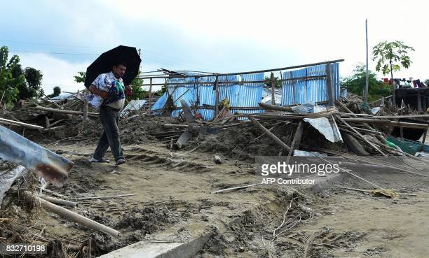 A man walks past damaged houses hit by flood in Itahari Sunsari district some 250 kms from Nepal's capital Kathmandu on August 16 2017 At least 221...