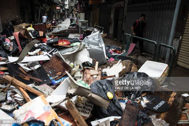 TOPSHOT A man walks past debris and rubbish piled up on a street in the aftermath of Typhoon Hato which hit on August 23 as severe tropical storm...