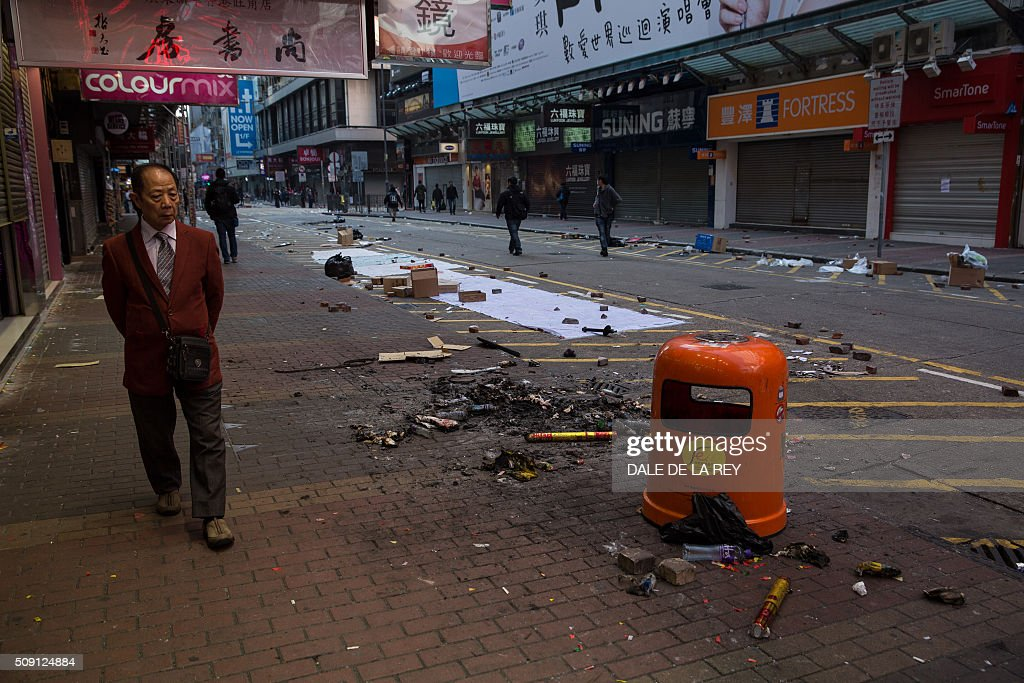 A man walks past debris following overnight clashes between protesters and police in the Mongkok area of Hong Kong on February 9, 2016. Baton-wielding Hong Kong riot police fired warning shots and tear gas early on February 9 after a riot erupted in the busy district of Mongkok when officials tried to shift illegal hawkers, local radio reported. AFP PHOTO / DALE DE LA REY / AFP / DALE de la REY