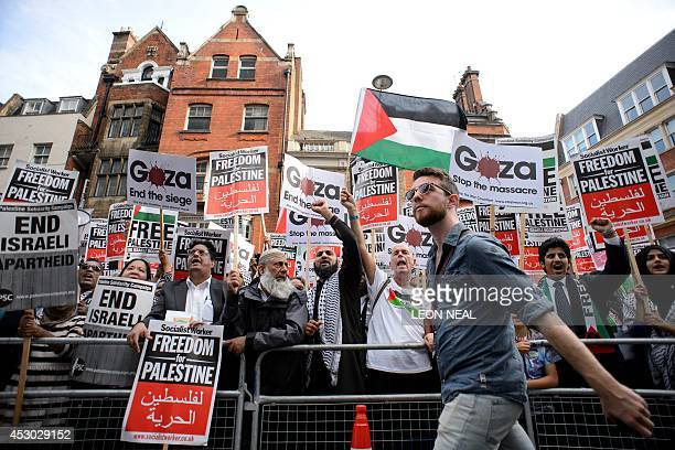 A man walks past demonstrators gathering near the Israeli embassy in central London on August 1 during a protest calling for an end to Israel's...