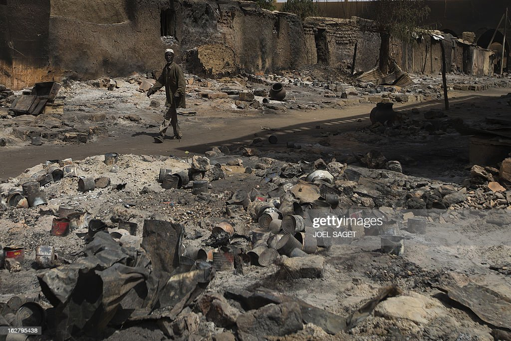 A man walks past destroyed buildings in a Gao's street on February 27, 2013. Chad's President Idriss Deby Itno on Wednesday urged the Malian army and West African force to speed up the deployment of troops to northern Mali to help fight Al-Qaeda-linked rebels.