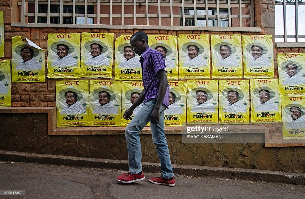 A man walks past election posters for incumbent President Yoweri Museveni in Kampala on February 11, 2016. Museveni is facing his hardest battle to remain president of the East African country in the forth coming presidential elections on February 18, 2016, as polls show his main rival Kizza Besigye and former Prime Minister Amama Mbabazi gaining increased public support. / AFP / ISAAC KASAMANI