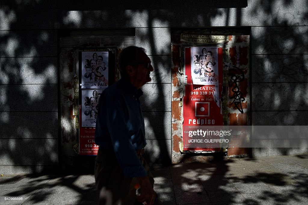 A man walks past electoral campaign posters of left-wing party Podemos on the eve of Spanish general elections in Madrid on June 24, 2016. Spain votes again on June 26, six months after an inconclusive election which saw parties unable to agree on a coalition government. / AFP / JORGE