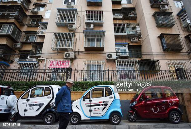 A man walks past electric cars and tricycles on a sidewalk in Beijing on April 25 2017 / AFP PHOTO / GREG BAKER