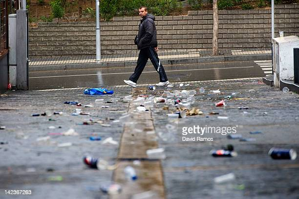 A man walks past empty beer cans plastic glasses and rubbish left by students after the second night of parties during the SalouFest on April 3 2012...