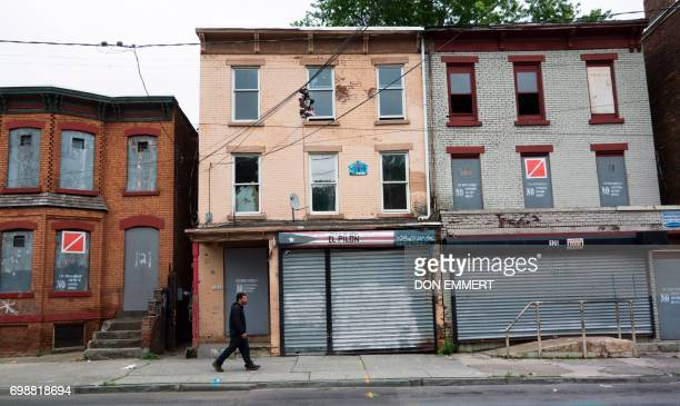 A man walks past empty homes with gray boards on the doors and windows on May 30 in Newburgh New York Rows of boardedup homes became a ubiquitous...