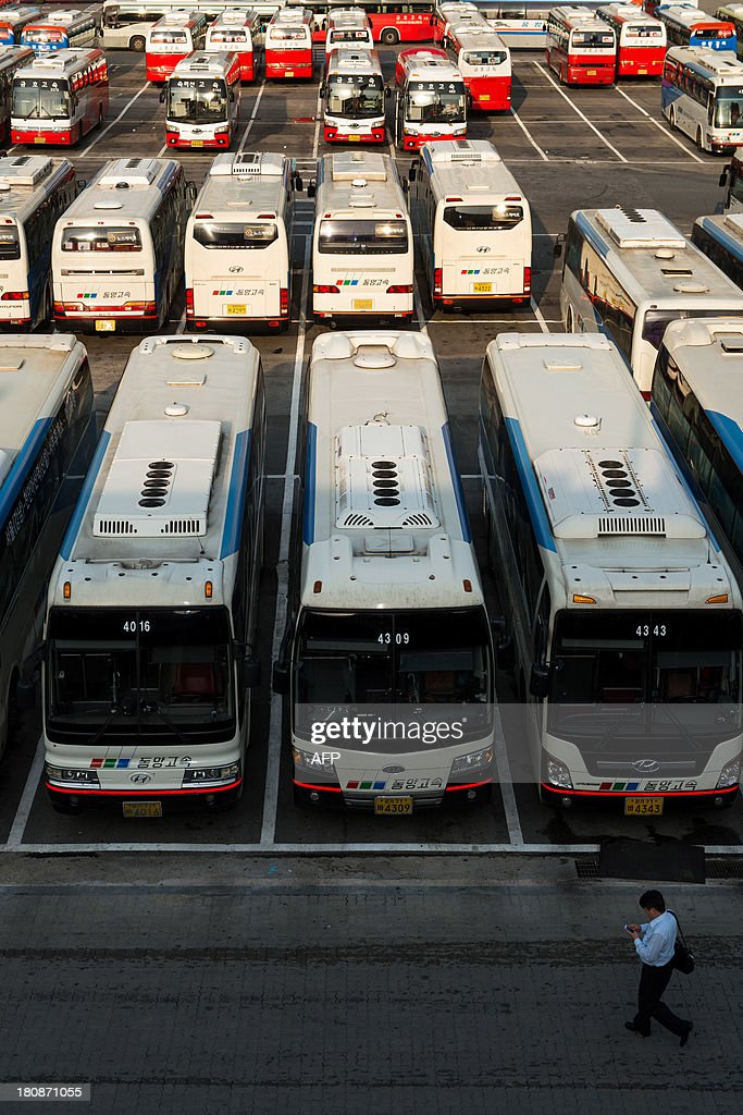 A man (bottom R) walks past express buses parked at Gangman express bus terminal in Seoul on September 17, 2013, ahead of Chuseok, South Korea's biggest holiday, which lasts from September 18-20. Approximately thirty five million people are expected to travel to their home towns and villages across the country to visit relatives this year, an increase of 4.9 percent compared with last year's holiday. AFP PHOTO / KIM DOO-HO